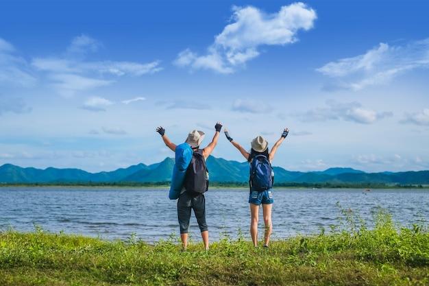 カップル旅行者は山の湖の近くに立っています。