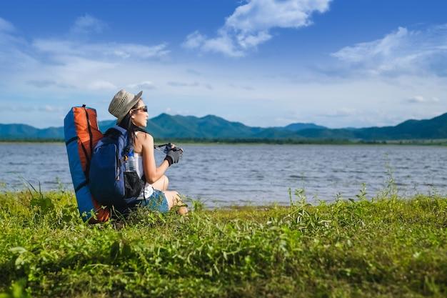 山の湖のそばに座っている女性旅行者