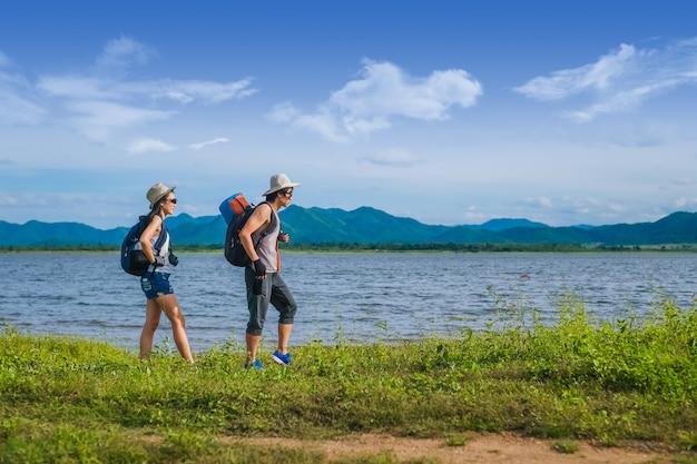山の湖の近くを歩くカップル旅行者