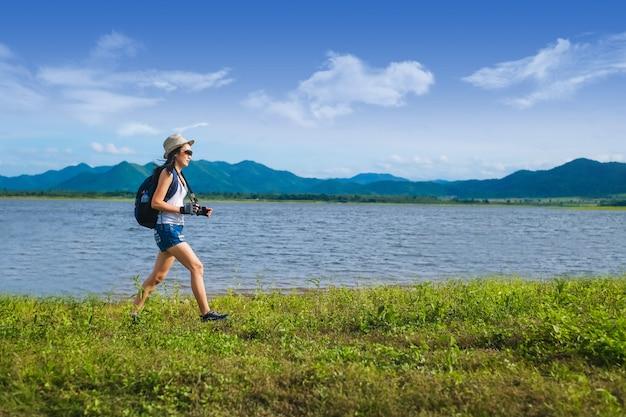 山の湖の近くに立っている女性旅行者