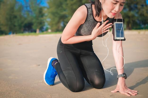 Азиатская женщина тренируется бегом по пляжу и имеет проблемы с сердцем