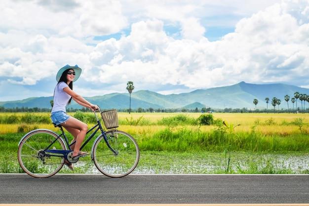 自転車に乗って休日に自然の景色を探しているアジアの女性観光客。