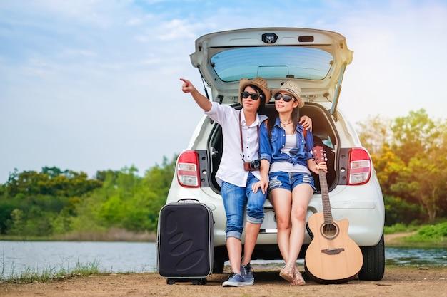 Пара путешественник, сидя на хэтчбек автомобиля и наслаждаясь видом на природу недалеко от озера