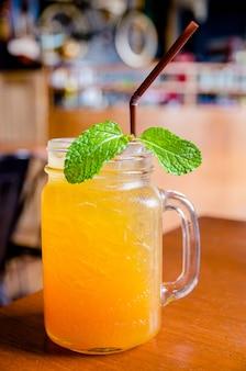 Замороженный чай в стеклянной бутылке с листьями мяты на деревянном столе