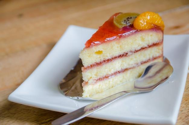 Кусок торта с клубникой на белой тарелке