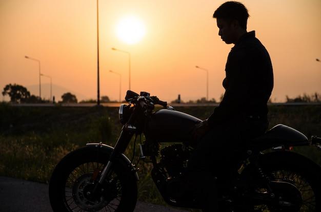 日没のシーンでビンテージバイクカフェレーサースタイルに乗って男のシルエット
