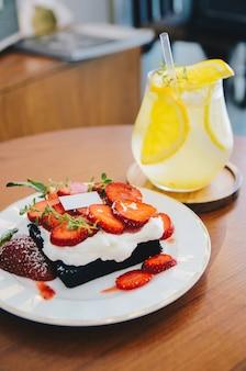 木製のテーブルにアイスクリームレモンとストロベリーケーキ