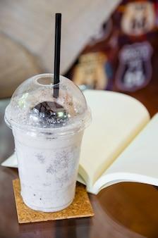 ガラステーブルの上の開いた本とミルクチョコレートのスムージー