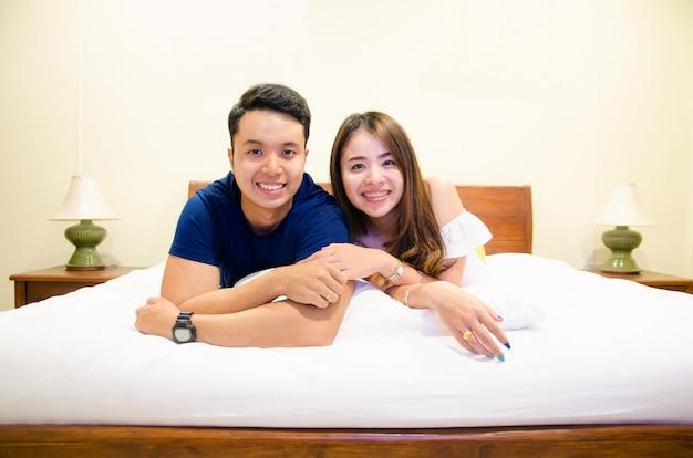 一緒に手を握って、ベッドに横になっているアジアカップル