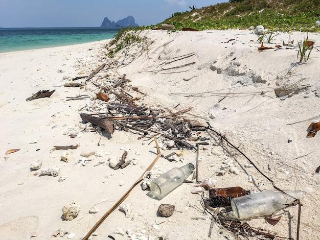 Стеклянная бутылка пластиковый мусор, пена и грязные отходы на пляже в летний день.