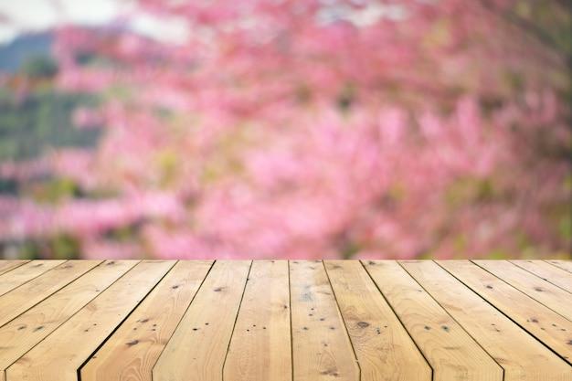 カラフルな花の背景をぼかした写真と空の木製テーブルトップ