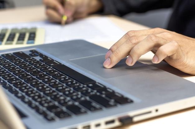若い男がノートパソコンで作業、ノートパソコンのタッチパッドに手します。
