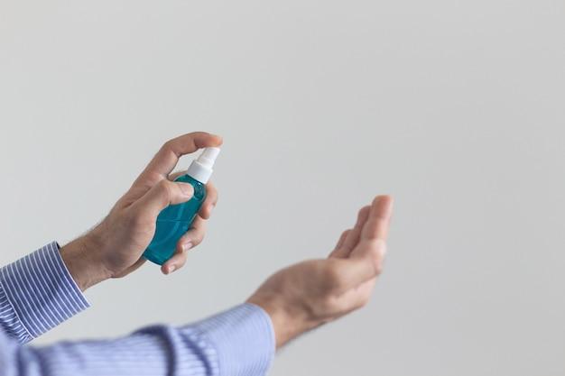 アルコールボトルの手にスプレーを保持している男の手の選択と集中