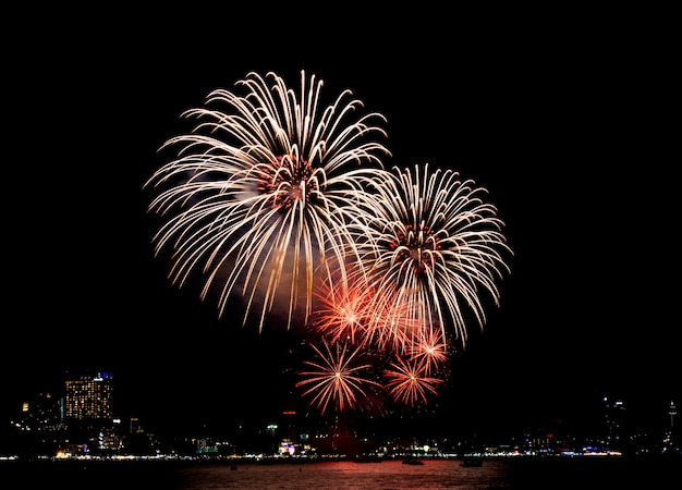 Фестиваль фейерверков в паттайе, таиланд. красочный фейерверк на ночном небе на пляже.