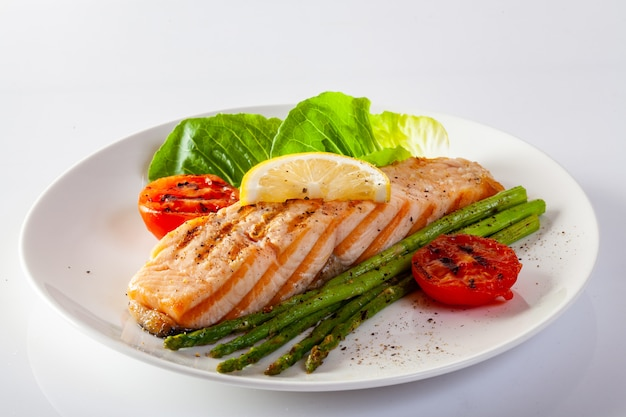 Жареный стейк из лосося с томатами аспарагос со свежими овощами.