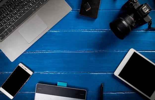 青い木製テーブルの平面図。写真家デスクトップの背景はコピー領域で機能します。