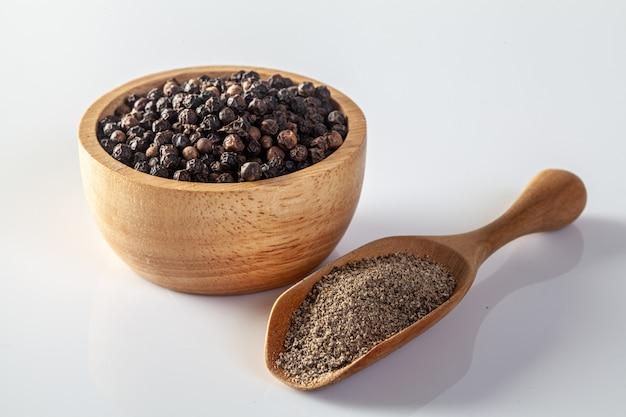 Черный перец и мельница для перца на белом фоне