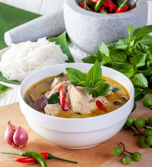 Зеленый карри с курицей на деревянном фоне, тайская кухня