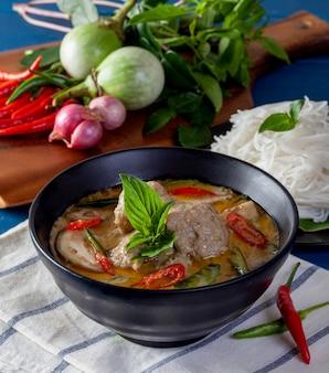 木製の背景、タイ料理に魚のボールとグリーンカレー