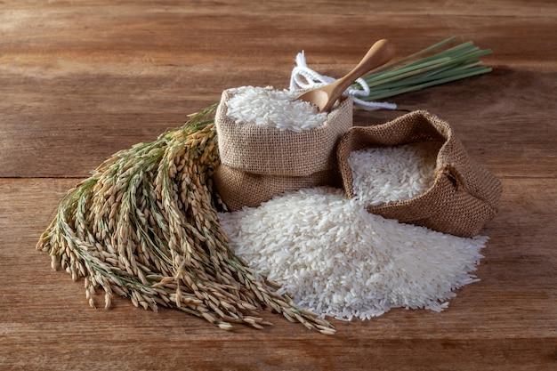 木製の背景に袋に白いご飯(ジャスミンライス)