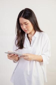 Красивая женщина, играя в социальные с планшетом на белой стене