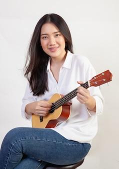 Красивая женщина представляя играющ гавайскую гитару на белой стене.