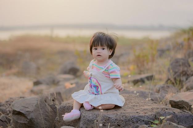 Красивый маленький ребенок сидит на скале.