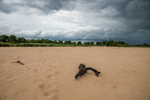 Темные облака и осадки от грозы над песчаной дюной в реке луны, сельский сурин, таиланд