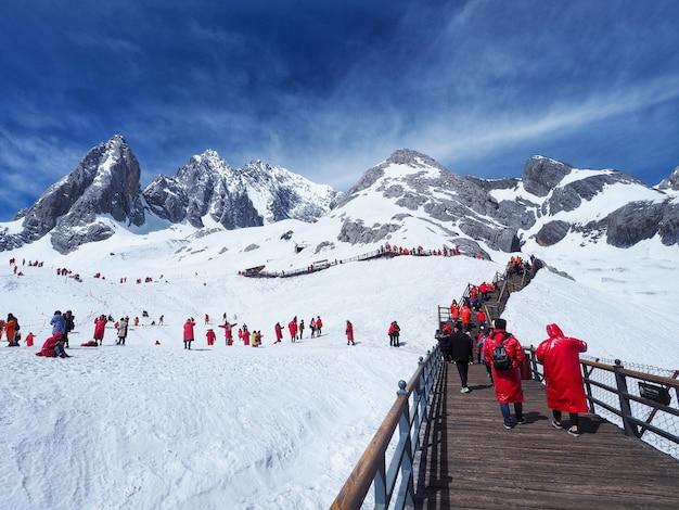 麗江、雲南省、中国の玉龍雪山と青空の観光客