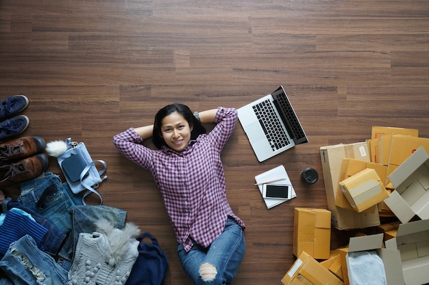 トップビュー中小企業経営者の女性は木製の床に横たわる