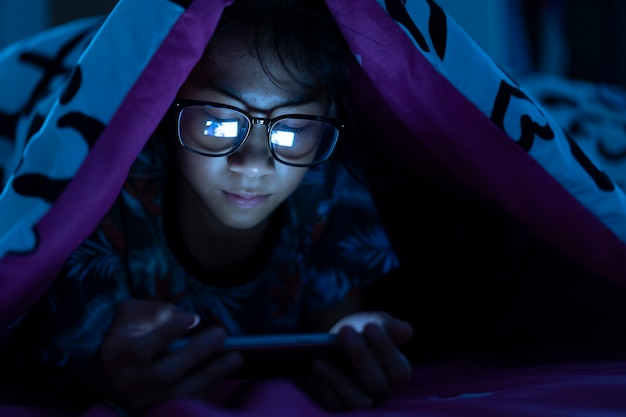女の子は、ベッドルームの暗いベッドで携帯電話を使用してメガネを着用