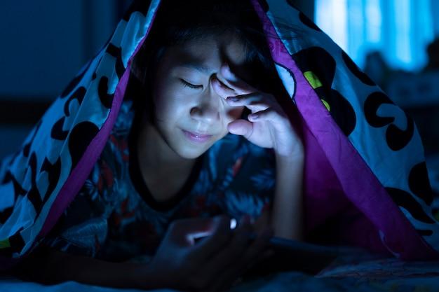 ベッドルームの暗いベッドで携帯電話を使っている少女