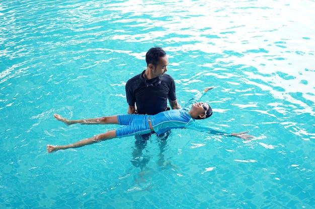 Отец учит дочь плавать