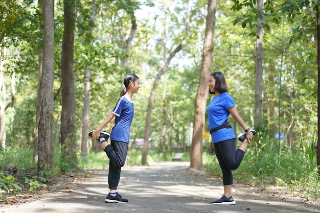 アジアの母と娘は公園で走る前にストレッチ太ももの筋肉をウォームアップ
