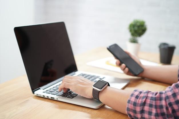 ラップトップコンピューターで作業して女性持株スマートフォンのクローズアップ