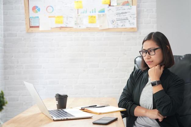 Азиатская женщина сидит в стильной наблюдая интересный тренинг вебинар онлайн портативный компьютер