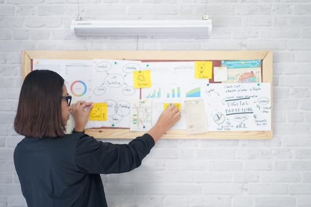 女性ビジネス女性または教師付箋チャートとボード上のグラフ