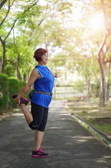 アジアの年配の女性は公園で音楽を聴きながら筋肉を伸ばします。