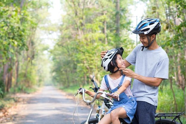 幸せな父と娘が公園でサイクリングしている彼の娘に自転車用ヘルメットをかぶっています。