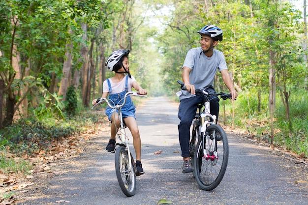 幸せな父と娘が公園でサイクリング