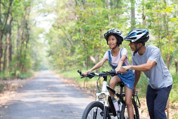 Счастливый отец и дочь на велосипеде в парке