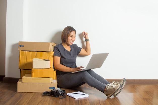 オンライン販売のアイデアコンセプトで、成功した女性、作業中のラップトップコンピューター