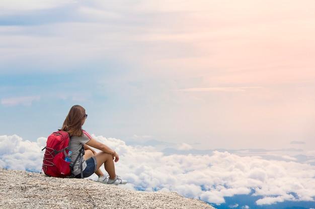 バックパックを持つ女性は日没で夏の山の霧に座る
