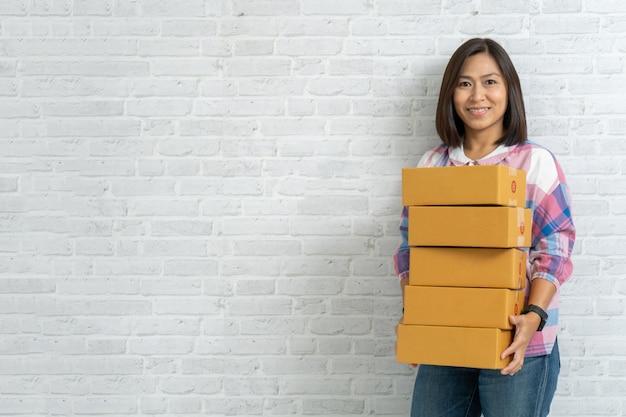 アジアの女性はレンガの壁に茶色の小包または段ボール箱を運ぶ