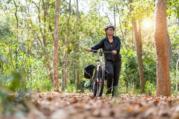 Привлекательная старшая азиатская женщина с велосипедом в парке