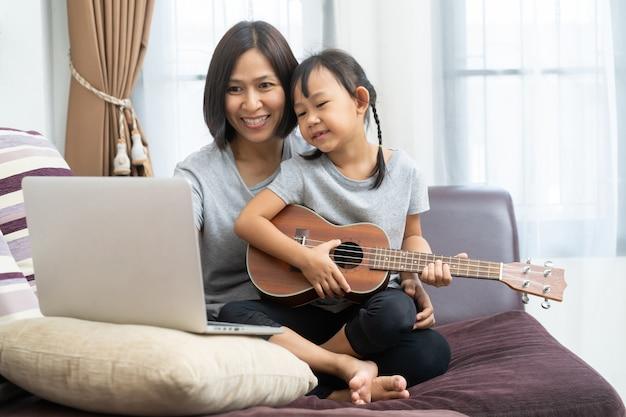 ノートパソコンと自宅でウクレレを使用してアジアの母と娘