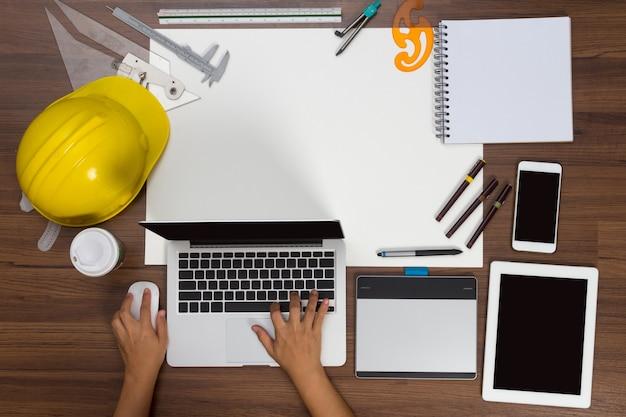 ノートパソコンの建設プロジェクトのアイデアの概念を使用して、オフィスのデスクの背景の手