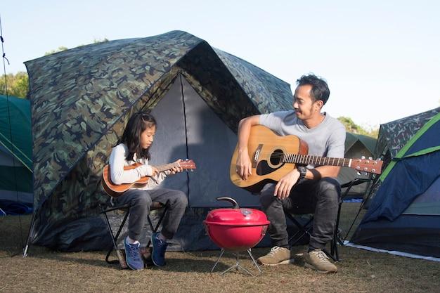 キャンプでウクレレとギターを演奏する父と娘
