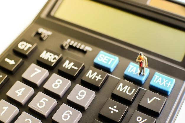 Миниатюрный бизнесмен стоя на голубой кнопке «налога» черного калькулятора с световым эффектом на левой верхней стороне используя как концепция возврата налога, финансов и дела.
