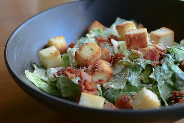 Вкусный салат цезарь с гренками, беконом и маслом с листьями салата с соусом